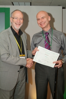 Dominic holding Fellowship Certificate